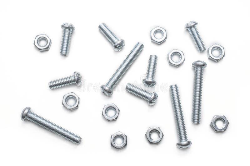 Macro de una pequeña colección de tornillos y de pernos del hierro en un Whitebox foto de archivo libre de regalías
