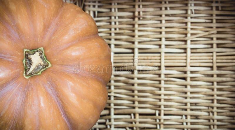 Macro de vue supérieure du beau potiron orange se reposant dans un panier en osier rustique, avec l'espace de copie Beau fond de  image stock