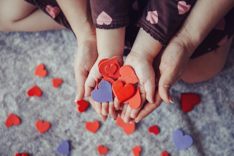 Macro del bambino con le palme adulte delle mani del genitore che tengono un mazzo di piccoli cuori di carta rossi e porpora dell immagini stock