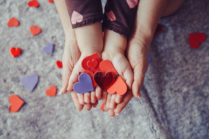 Macro del bambino con le palme adulte delle mani del genitore che tengono un mazzo di piccoli cuori di carta rossi e porpora dell fotografie stock