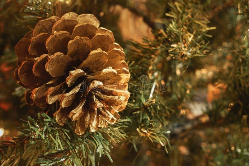 Macro del pinecone de oro en árbol de navidad artificial, con el espacio borroso del fondo y de la copia imagen de archivo