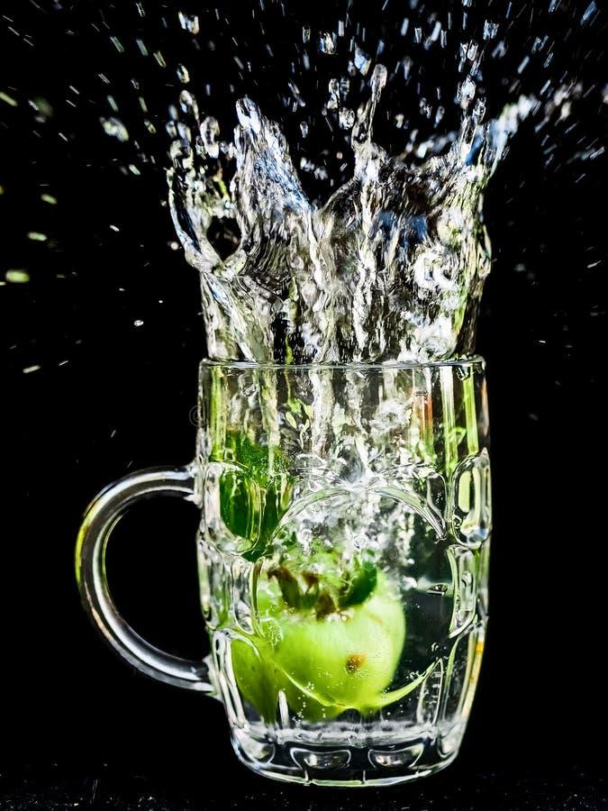 Macro del primo piano della spruzzata dell'acqua della mela fotografie stock libere da diritti