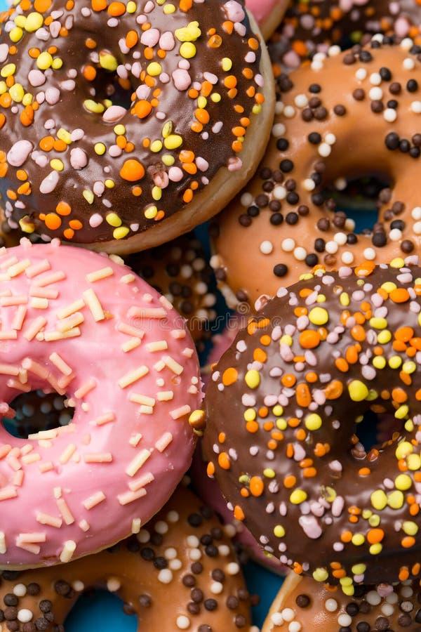 Macro delicious donuts colored glaze in sunlight stock image