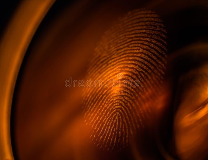 Macro dell'impronta digitale su una lente alla luce rossa fotografie stock libere da diritti