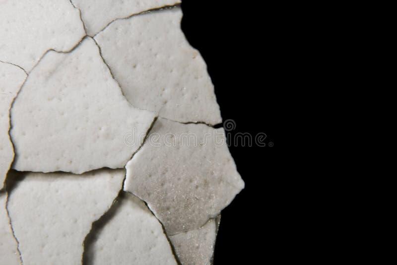 Macro delle coperture incrinate dell'uovo su un fondo nero fotografia stock