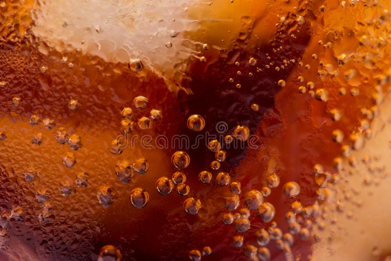 Macro des bulles et du sifflement Un verre frais de boisson de kola avec de la glace photo libre de droits