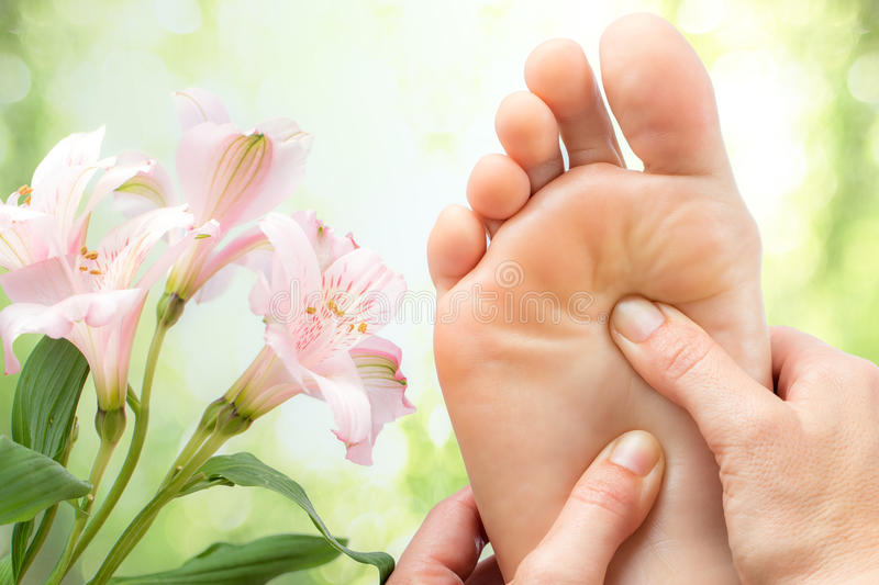 Macro detail of foot massage next to flowers. Macro close up of foot massage next to colorful flowers and green background stock photos