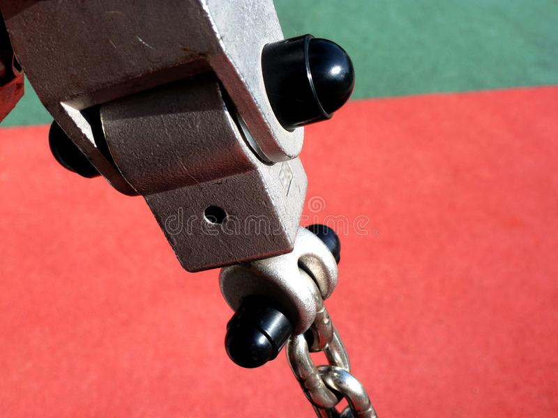 Closeup detail of shiny steel chain swing hanger. Macro detail of shiny steel swing chain and connection in diminishing perspective with blurry colorful stock photography