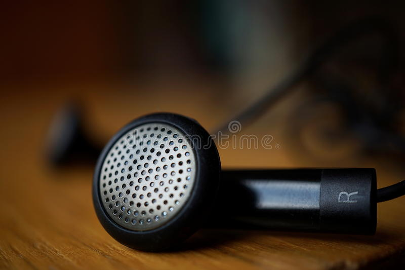 Macro detail of a silver and black perforated headphones (ear-buds) with cables. Macro detail of silver and black perforated headphones (ear-buds) with cables royalty free stock photography