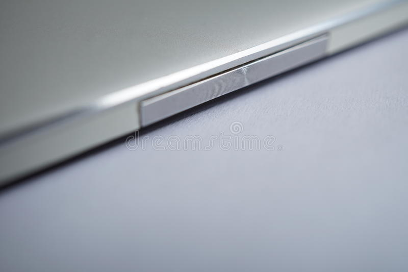 Macro detail of a silver rocker switch button made of brushed aluminum in the modern smart phone with shiny beveled edges. Macro detail of silver rocker switch stock photography