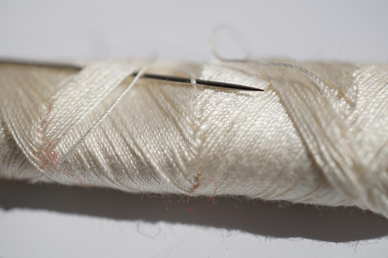 Macro detail of a silver sharp needle inserted in the spool of white thread stock photography
