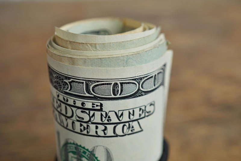 Macro dettaglio di un rotolo verde di valuta americana USD, dollari americani con 100 dollari di banconota sull'esterno come simb fotografia stock