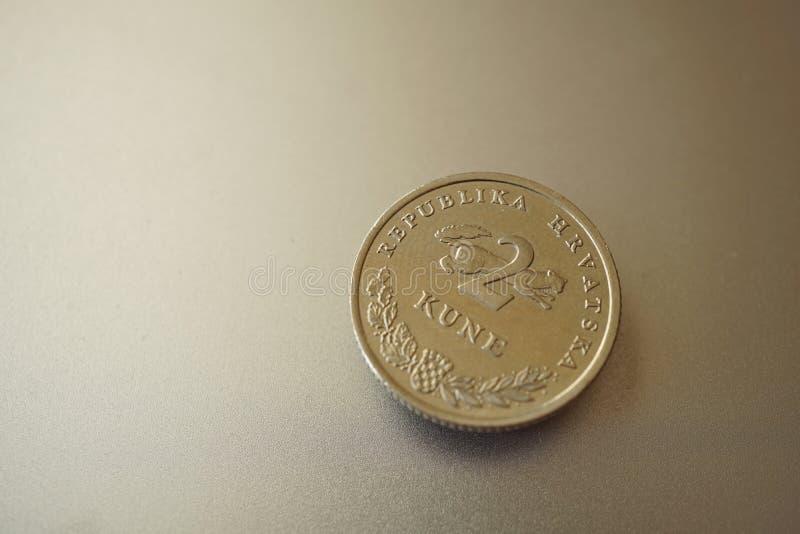 Macro dettaglio di una moneta del metallo & di un x28 croati; 2 Kune& x29; sui precedenti d'argento brillanti del metallo fotografia stock libera da diritti