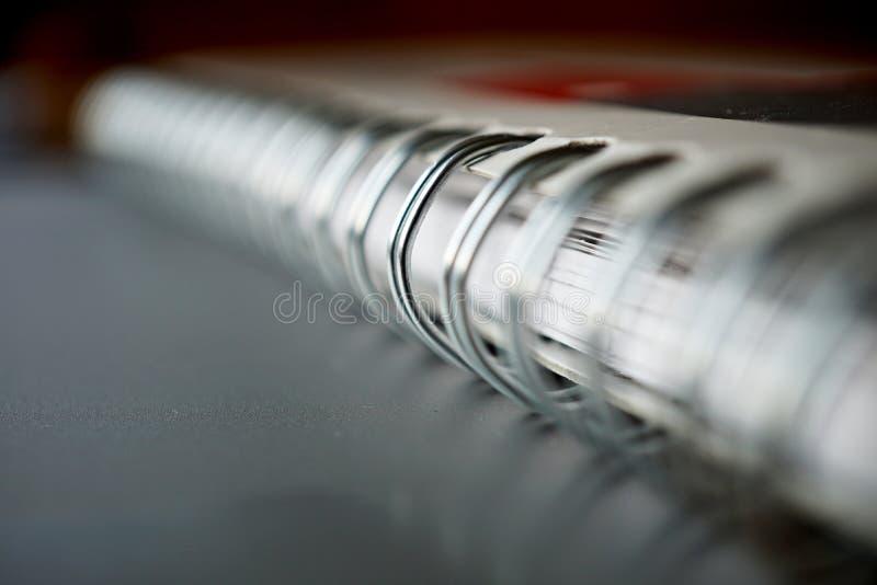 Macro dettaglio di una spirale obbligatoria del metallo del blocco note bianco sulla superficie d'argento immagine stock libera da diritti