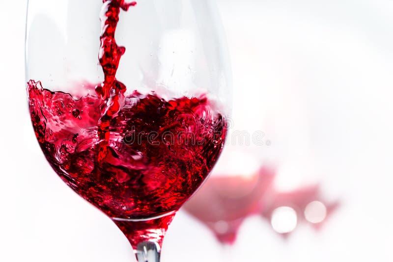 Macro dichte omhooggaand van rode wijn het inschenken aan glas stock foto