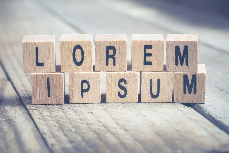 Macro du lorem ipsum de mots constitué par les blocs en bois sur un plancher en bois images libres de droits