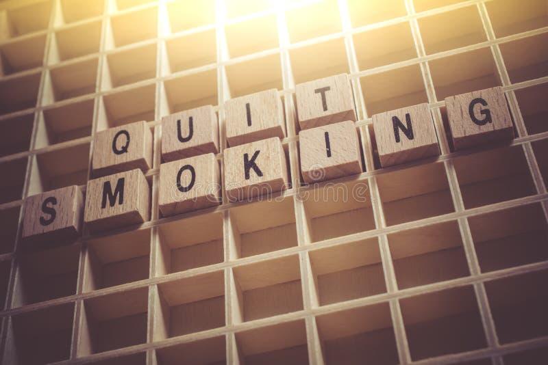 Macro du tabagisme stoppé par mots constitué par les blocs en bois dans un Typecase photos stock