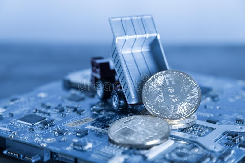 Macro Dump Truck On Blue Computer Motherboard Background. Dumpi. Ng Silver Bitcoin Mining Concept stock photography