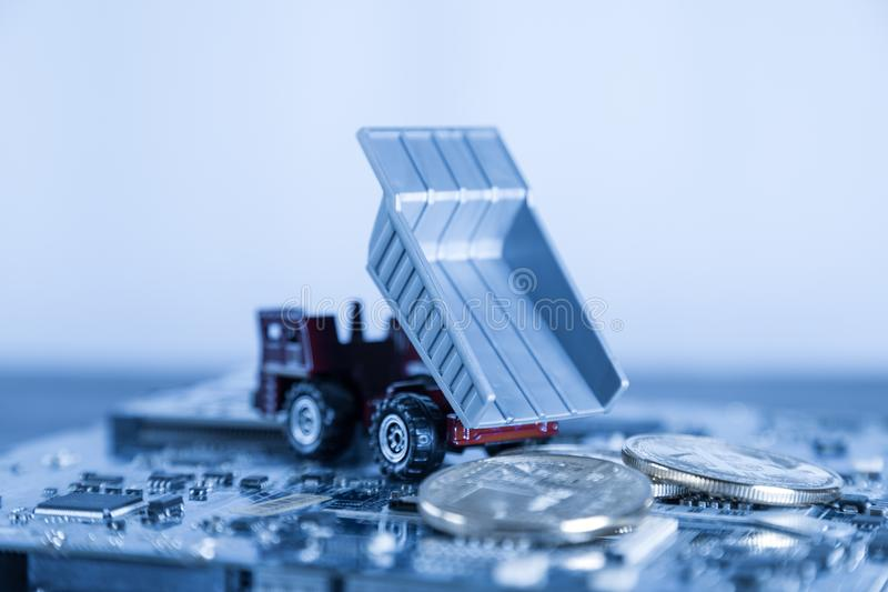 Macro Dump Truck On Blue Computer Motherboard Background. Dumpi. Ng Silver Bitcoin Mining Concept stock images