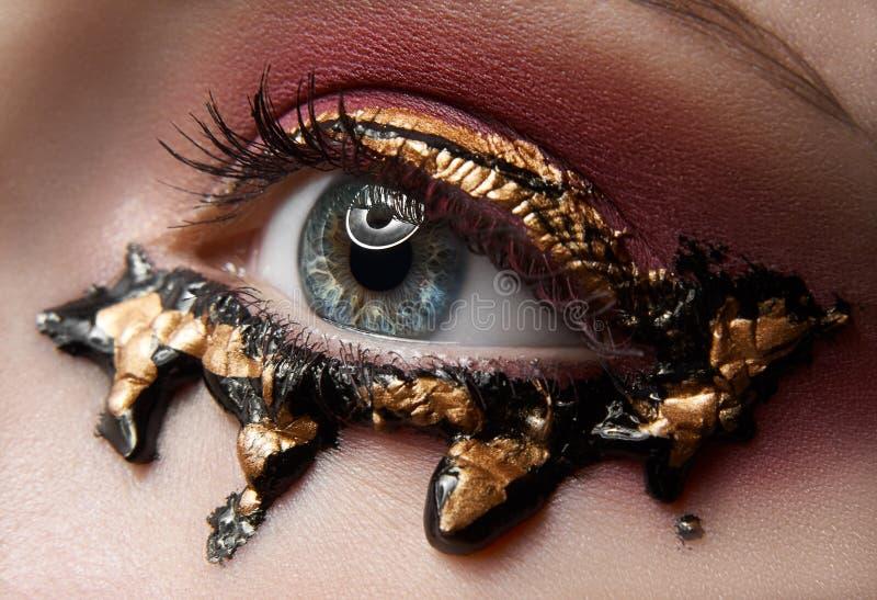 Macro e tema creativo di trucco del primo piano: bello occhio femminile con le ombre e l'oro rossi, pittura nera, foto ritoccata fotografie stock