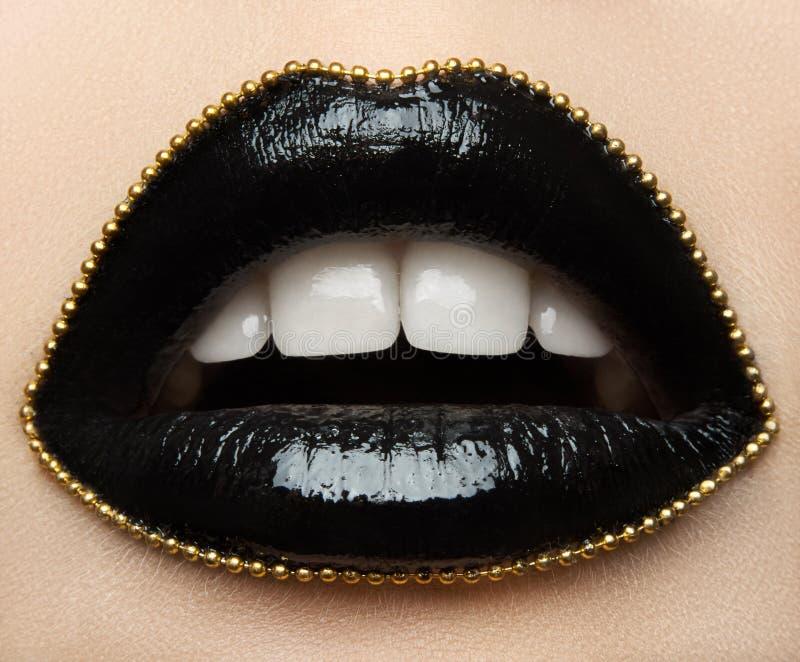 Macro en close-up als thema heeft de creatieve samenstelling: de mooie vrouwelijke lippen met zwarte lippenstift en een goud kete royalty-vrije stock afbeeldingen