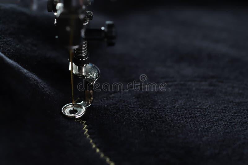 Macro en la aguja de la perforación de la máquina del bordado en del negro la tela velvetely para coser motivo del cerdo con hila imagen de archivo