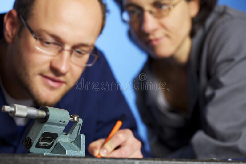 Macro of engineer recording measurements with assi stock images