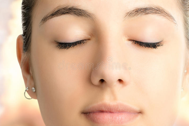 Macro face shot of woman meditating with eyes closed. stock photography