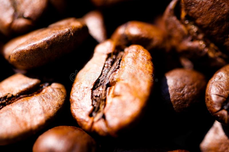 Macro fin de la pile des grains de café bruns rôtis à la lumière du soleil naturelle montrant des détails de la surface photo stock