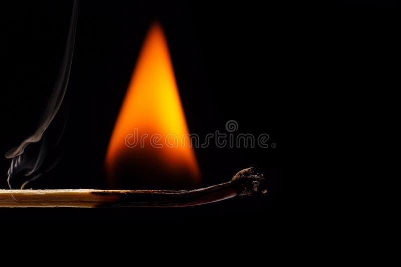 Macro fire burning on matchstick. Studio shot isolated on black stock images