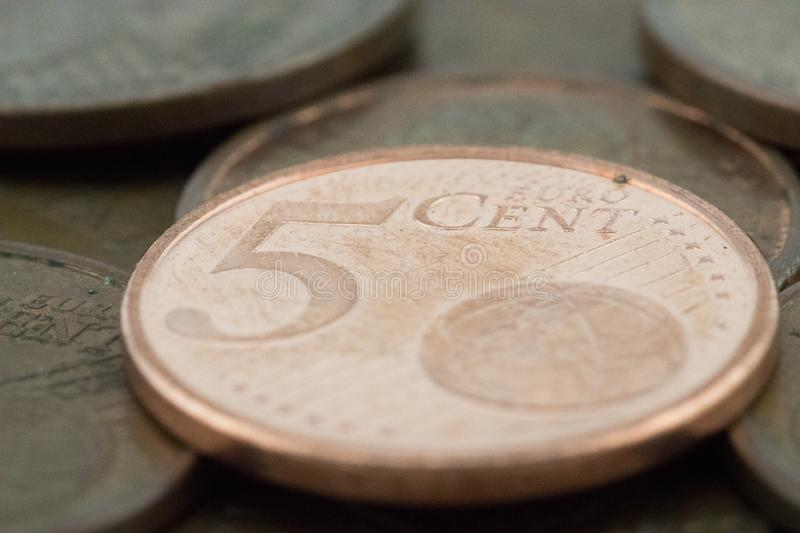Macro of a five euro cent coin supported on more bronze coins royalty free stock photography