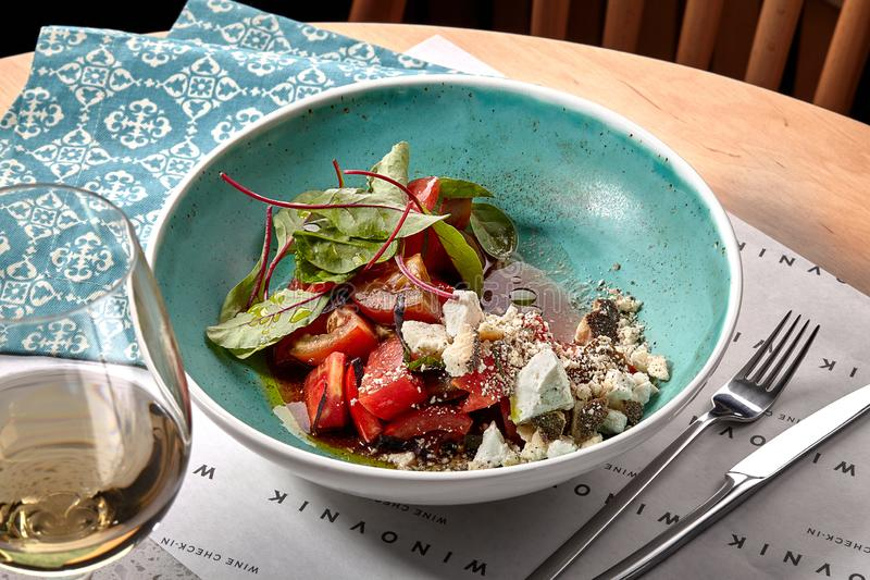 Macro foto di Salat di verdure tradizionale con i pomodori, il formaggio a pasta molle, il coriandolo e Olive Oil affettati fotografie stock