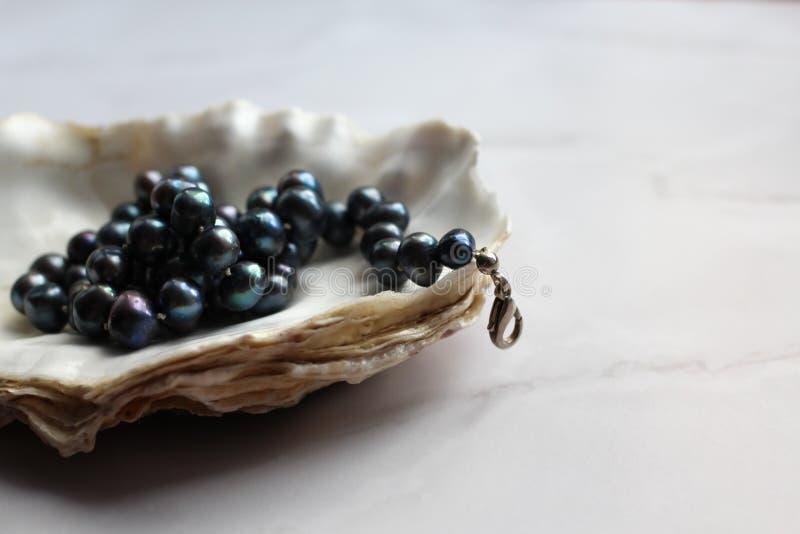 Macro fotografia delle perle nere della perla con le pietre preziose sulle coperture, fondo di marmo immagine stock