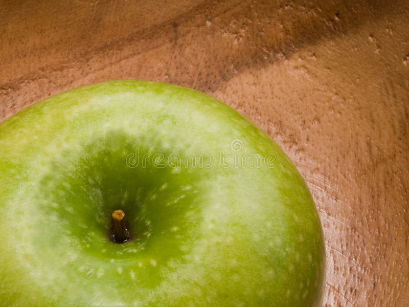 Macro of fresh green apple on wooden dish royalty free stock photo
