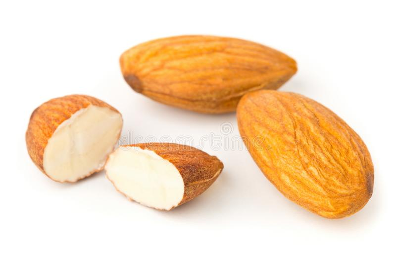 Macro of full and halfed shelled almond kernels. With selective focus over white background stock photos
