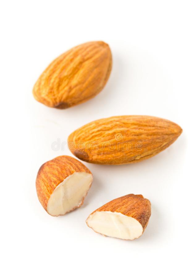 Macro of full and halfed shelled almond kernels. With selective focus over white background royalty free stock photography