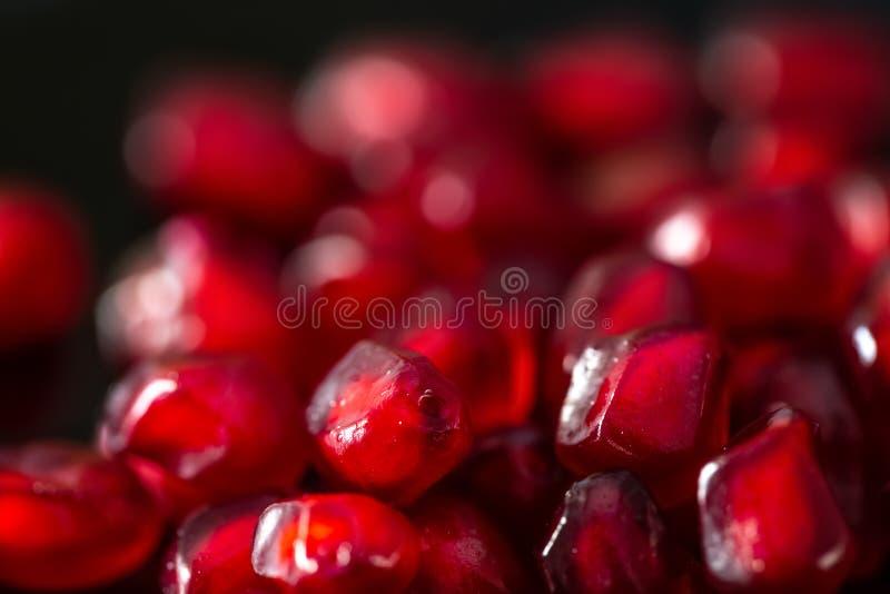 Macro Fundo obscuro bonito com a romã vermelha das grões fotos de stock