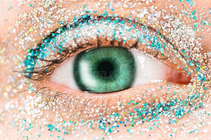 Macro green female eye with glitter eyeshadow, colorful sparks, crystals. Beauty background, fashion glamour makeup stock image