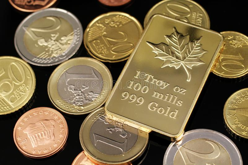 A close up image of Euro coins with a Canadian gold ingot on a black background royalty free stock photography
