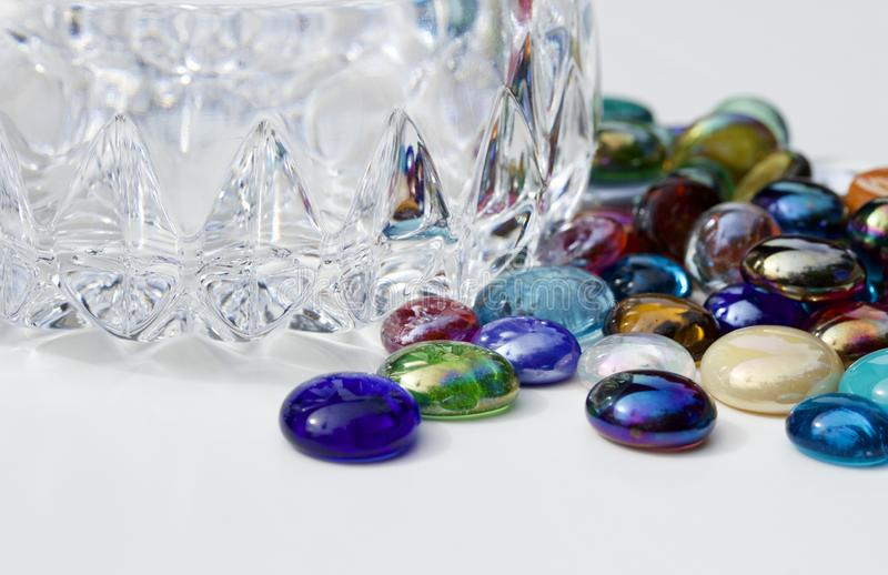Macro image of colorful dragon tears glass stones surrounding a small crystal bowl. This image shows a closeup view of multi color dragon tears glass stones royalty free stock photos