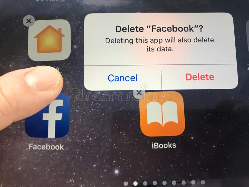 Macro image of a finger about to delete the Facebook app from an iPad screen - might be due to data privacy issues stock photos