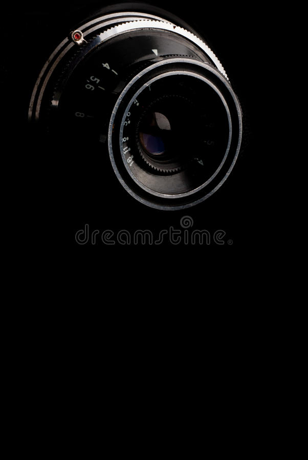 Macro image of lens on retro camera. Over black background stock photo