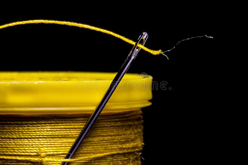 A macro image of a needle's eye threaded with a piece of yellow thread on a field of solid black.  The needle is entrapped in stock photos