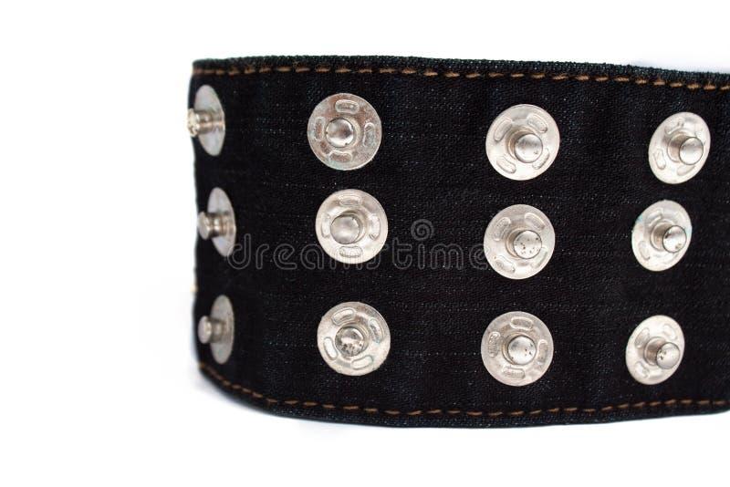 Macro immagine della cinghia nera dei jeans con molti bottoni su un fondo bianco, spazio della copia fotografia stock libera da diritti
