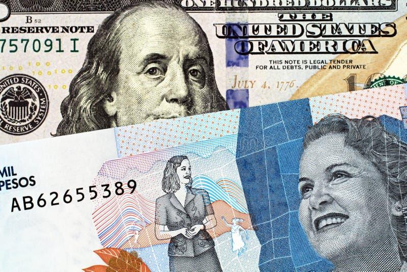 Macro immagine delle due mila note del peso di Colmbian con le cento banconote in dollari americana immagini stock libere da diritti