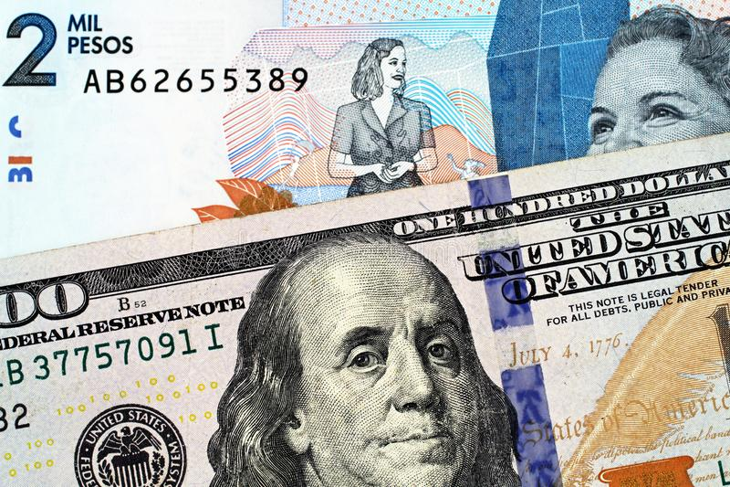 Macro immagine delle due mila note del peso di Colmbian con le cento banconote in dollari americana fotografia stock