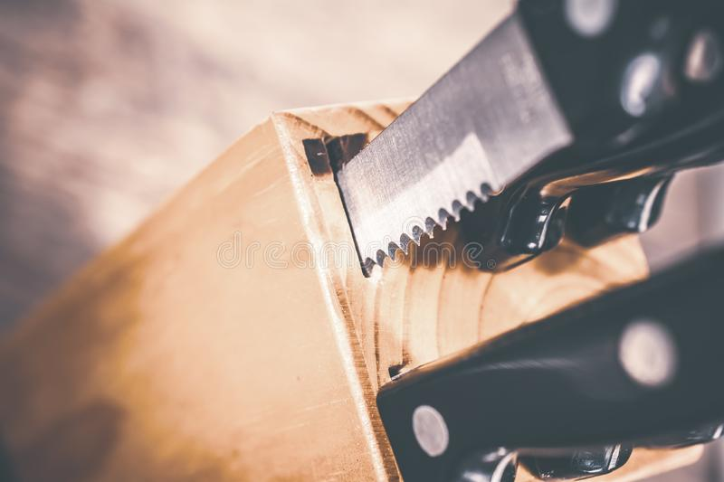 Macro Of A Jagged Steak Knife Half Pulled Out Of A Kitchen Knive Block On A Table royalty free stock images
