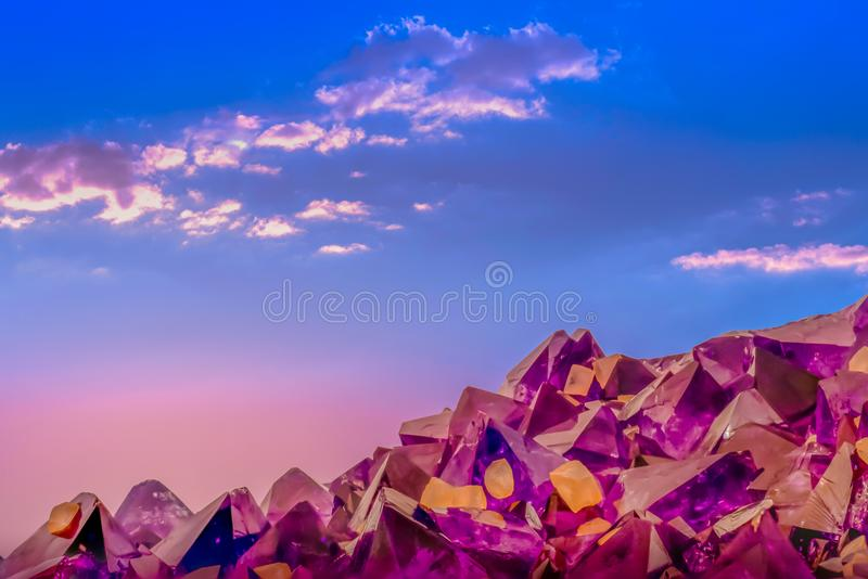Macro photo of amethyst crystals and sunset sky with clouds royalty free stock images
