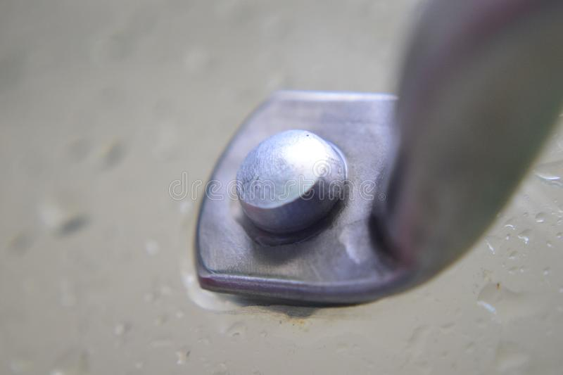Macro bolt on cover. A macro photo of a bolt on the handle of a frying pan lid cover stock photos