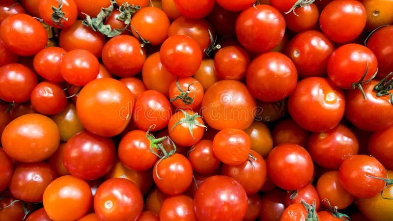 Macro image of lots of red small cherry tomatoes on counter at vegetable store. Texture or pattern of fresh ripe. Macro photo of lots of red small cherry royalty free stock photos